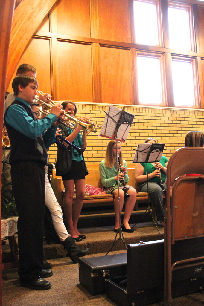 Local youth playing in band in church.
