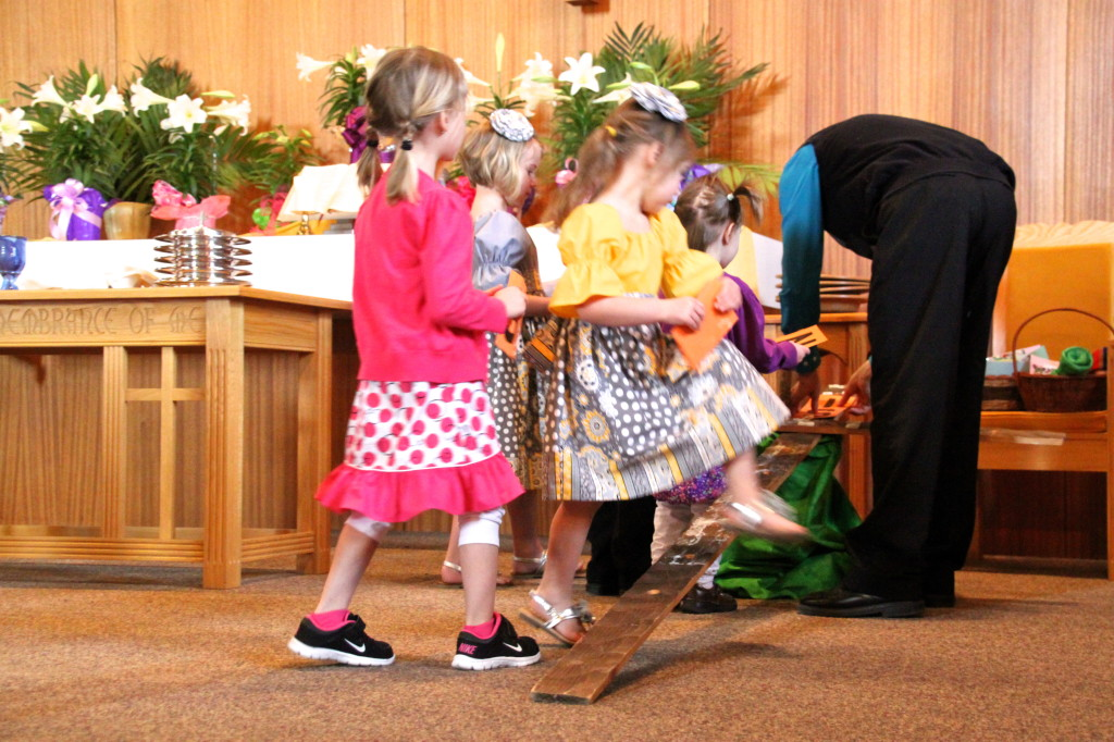 "Putting their letters of ""He Is Risen"" and flowers on the cross"
